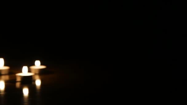 Sklenice na víno a hořící svíčky
