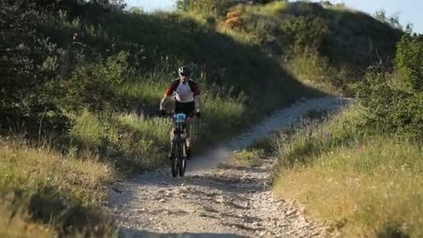 Mužský cyklisty, jízdu na horské cestě na horském kole.
