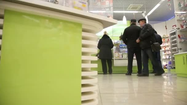People near counter in pharmacy drugstore.