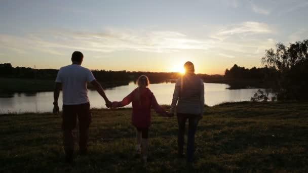 Siluette della gente sul tramonto di estate