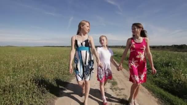 Mutter und Töchter gehen Händchen haltend
