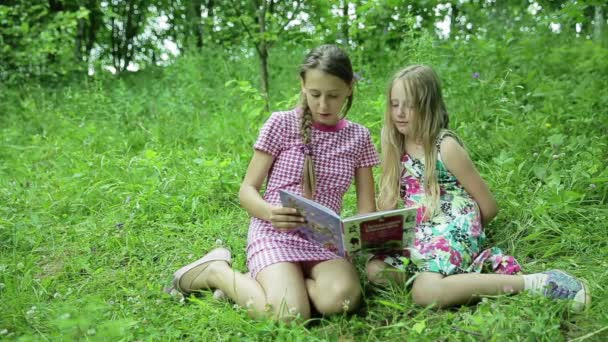 Two girls reading book in the park
