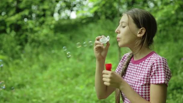 Mladá dívka foukání mýdlové bubliny venkovní