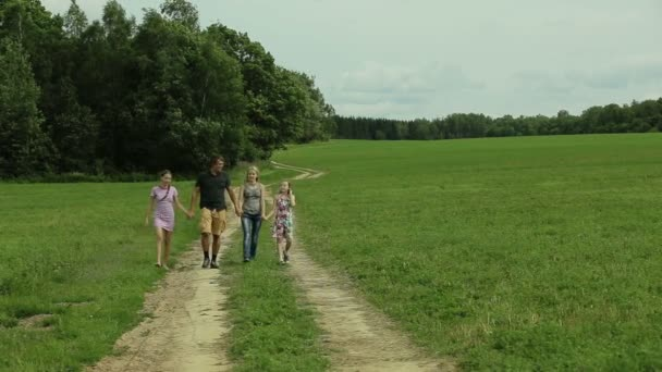 Šťastné rodiny chodící venkovské silnici drží za ruce
