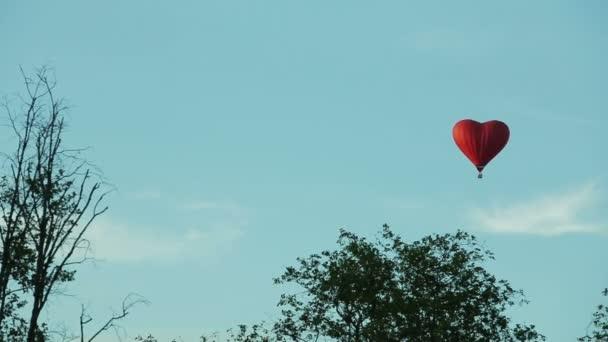 balon srdce na modré obloze nad stromy
