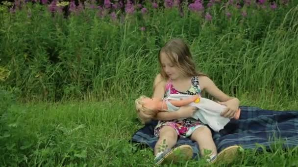 mladá dívka si hraje s panenkou na vnější trávy