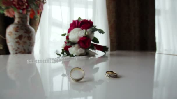 Rotating wedding rings near bouquet on the piano