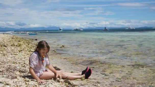 Šťastné dítě hraje s pískem na pláži v létě