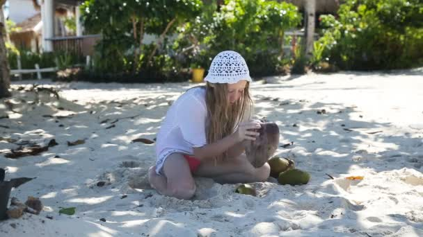 young girl playing with coconut on the beach.
