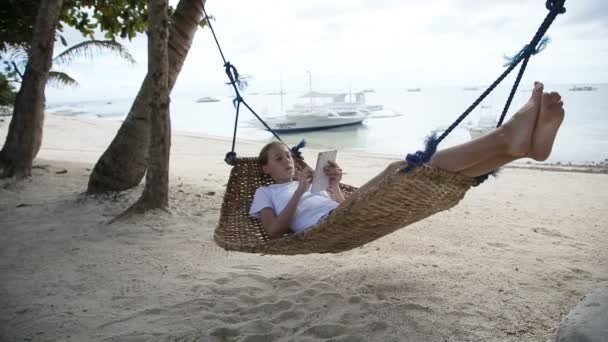 Girl in the hammock with the tablet on the beach