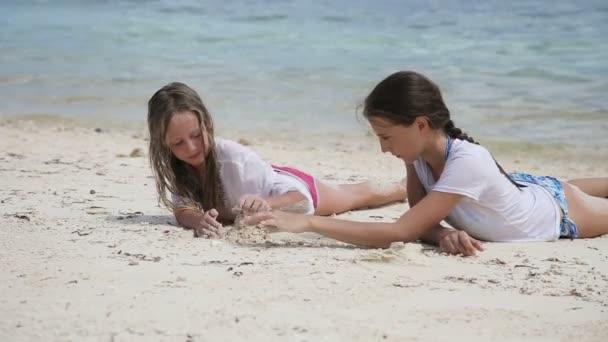 Šťastné holky hrají s pískem na pláži v létě