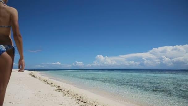 Two girls walking on a tropical beach