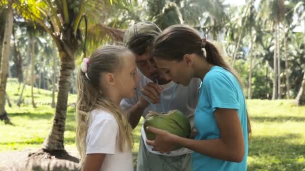 Young girls with father drinking coconut juice