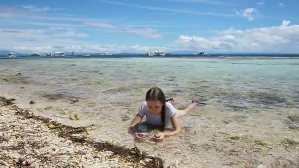 Boldog gyermek játszó homokos tengerparton nyáron.