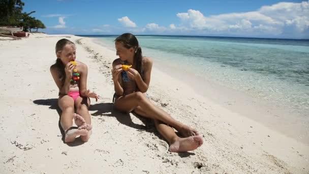 Fiatal lányok a parton, eszik mangó gyümölcs