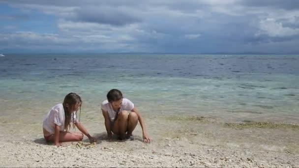 Boldog lány játszik a homok tengerparton nyáron