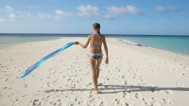 Girl with silk fabric walking along the beach