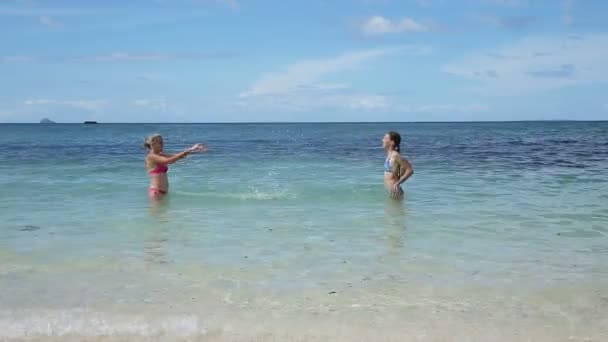 Mutter und Tochter spielen im Meer