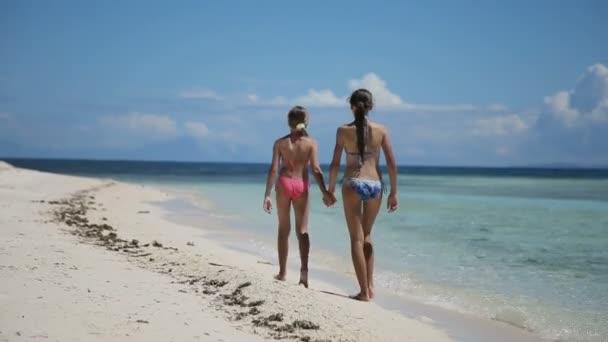 Két lány séta egy trópusi tengerparton