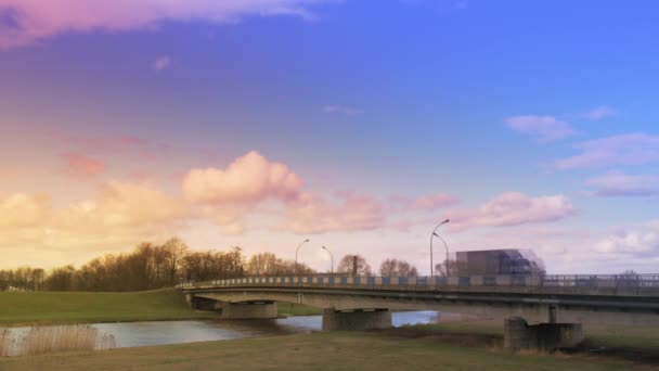 Car Bridge on Pink Sunset Cars Lorries Are Driven by a Concrete Bridge  Through Small River Hyper Lapse Time Lapse White Cumulus on Blue Sky Green  Meadows