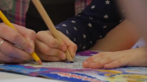 Žena je obraz s Kid v barvení kniha žlutou tužkou ruce zblízka dítě holčička a její pedagog v kostkované košili jsou malby jiné dítě přijde