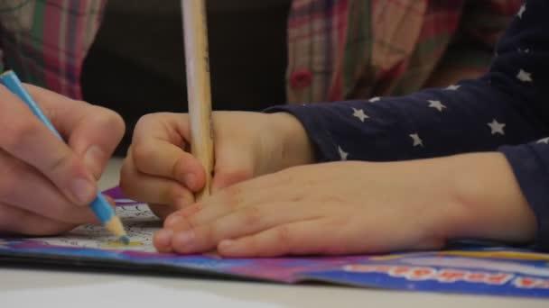 Učitel je obraz s Kid v barvení kniha s tužky ruce zblízka Kid a její vychovatel v kostkované košili jsou malby s Blue tužky