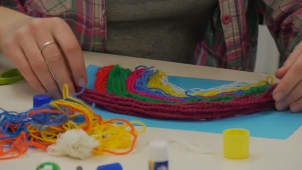 Ženské ruce jsou lepení víno vlákna papíru pomáhá, dítě děti dělají Rainbow barevných nití, sedí u stolu v učebně