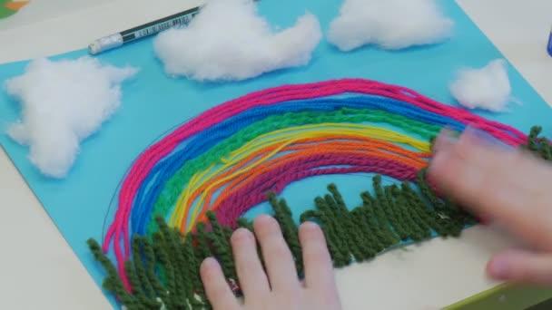Le mani del bambino prendere un arcobaleno applique di filati