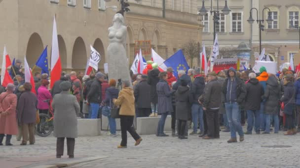 Democracy Defense Committee Meeting Poland Statue at Square People Are Holding Polish Flags Swaying With Placards Banners Standing at Vintage Building
