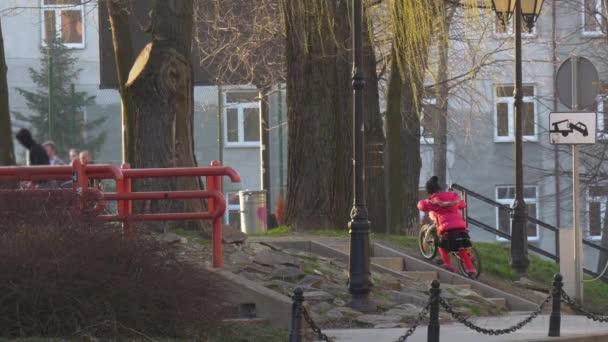 Kislány vezeti fel a hegy lovaglás kerékpár kerékpár város utca vagy a parkban, az esti aszfaltozott út az emberek sétálnak egy Park gyerek-rózsaszín