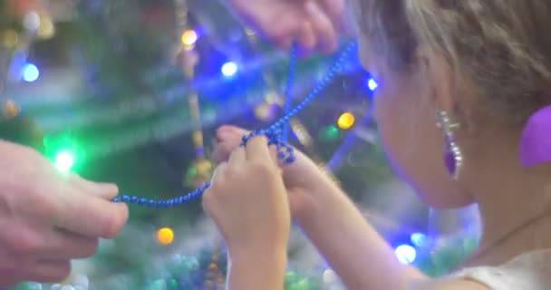 Girl and Her Father Untie a Blue Beads Garland Going to Put it to New-Year Tree Pine Golden Garland and Colorful Lamplights Family Celebration