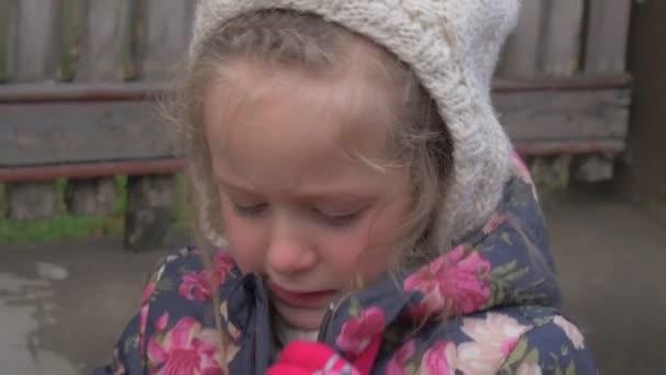 Smutné, že dívka dítě stěžuje rozhovory pláče malé dítě hraje venku blond kluk v květované bundě a bílý klobouk červený obličej dívka pláče, rozváže její zimní šála