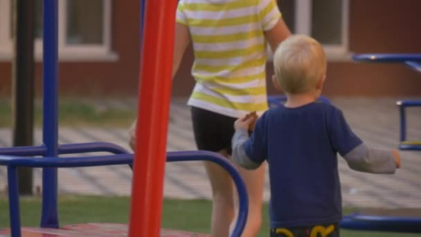 Children Are at The Playground at The Yard, Playing, Swinging, Girl Helps the Little Boy to Seat on a Swing, Blonde Girl in Pink Blouse on Foreground
