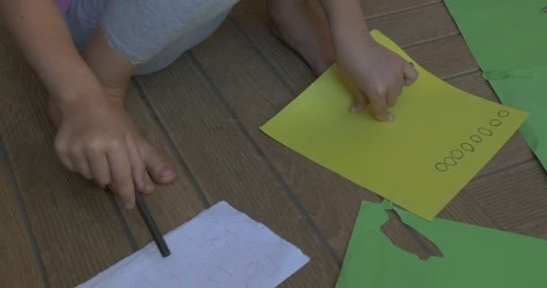 Little Girl With Blond Hair, in Pink T-Shirt And Gray Trousers, Is Sitting on a Floor, Drawing on the Yellow Sheet of Paper, Cutting Out the Circles