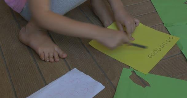 Holčička s plavými vlasy, růžové tričko a šedé kalhoty, sedí na podlaze, na žlutý list papíru, vysekávání kruhy