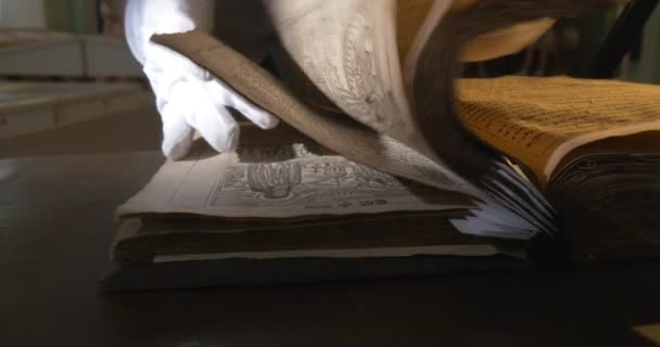 Muže v bílých rukavicích je vzrušením prostřednictvím stará kniha, drží knihu, vyhledávání, stránky s obrázky Closeup, Ray of Light na knihu, Darkness