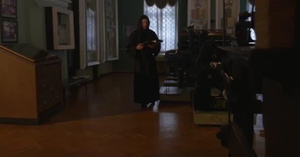Mnich je chůze s kniha The místnost s hnědé dřevěné podlahy, nábytek, okna, obrázky, člověk je čtení