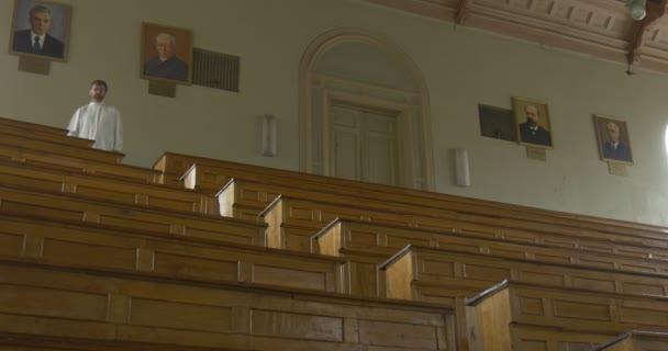 Pane profesore, chemik, biolog, učitel je chůzi dolů po schodech na amfiteátr Auditorim Hall, portréty jsou na zdi