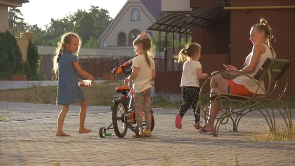 Děti hrají na dětské hřiště, na dvoře, děti, holka drží jízdní kolo, na kolo, máma sedí na lavičce