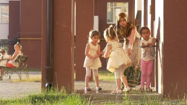 Woman In Hijab, Scarf, is Walking With Kids, Children Are Playing on a Children Playground, Two Girls-Twins, Kids are Washing their Hands
