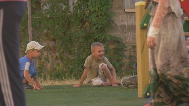 Chlapci, děcka, děti si hrají na dětské hřiště, sedící v trávě, smích, skákání, zpomalené