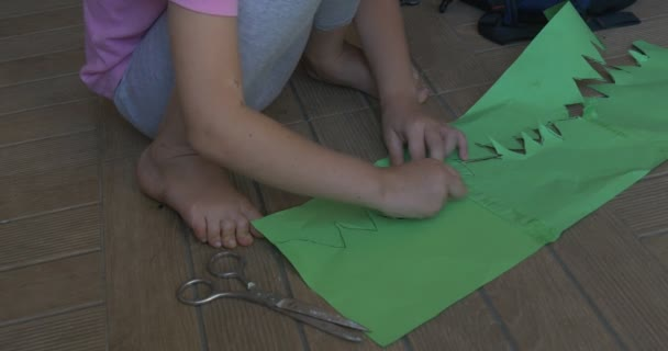 Little Girl in Pink T-Shirt With Blonde Braid is Sitting on the Floor, Cutting, Making a Figure from Color Paper, Cutting the Green Paper by Scissors