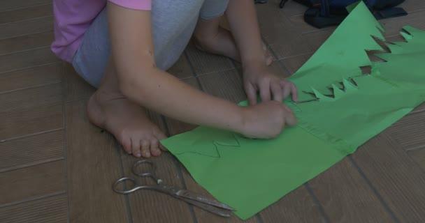 Holčička v růžové tričko s blond cop a sedí na podlaze, řezání, takže postava z barevných papírů, řezání na zelenou knihu o nůžky