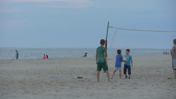 Lidi, děti, rodiny jsou v The Sandy Beach, hraní, odpočívá, běh, podvečer, skupiny dětí se hrát fotbal, volejbal čisté