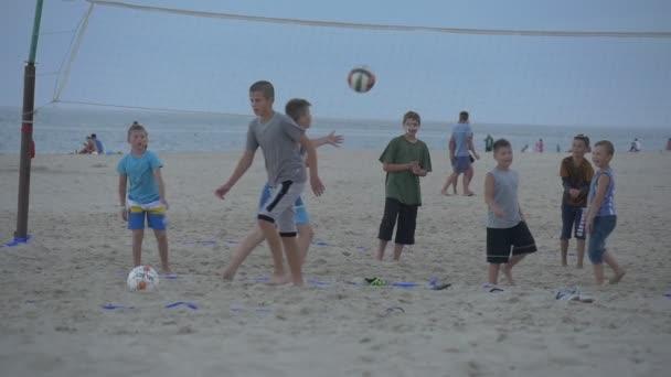Lidi, děti jsou spuštěny, dospívající chlapci hrají fotbal v Sandy Beach, nedaleko volejbal Net, kopnout míč, lidé hrát volejbal