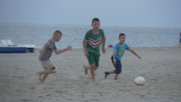 Lidi, děti jsou spuštěny, dospívající chlapci hrají fotbal v Sandy Beach, nedaleko volejbal Net, vlevo, sledování, sledování kopnout do míče