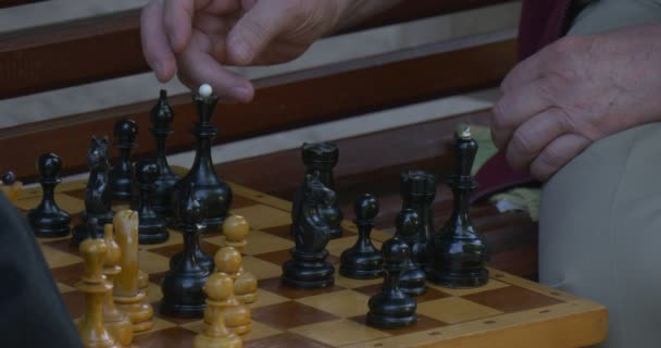 Two Men Are Sitting in Front of Each Other on The Bench, Playing Chess, Turn Chess Clocks on, Chess Board Closeup, Mens Hands, Moves the Chess Queen
