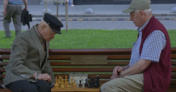 Two Men Are Sitting in Front of Each Other on The Bench, Senior Aged Men in Caps, Playing Chess, Mid Shot, Take the Turns Fast