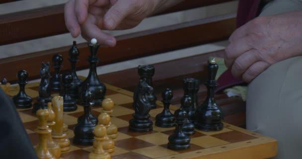 Zwei Männer sitzen voreinander auf der Bank, spielen Schach, Schachuhren einschalten, Schachbrett Nahaufnahme, Herrenhände, bewegt die Schachkönigin