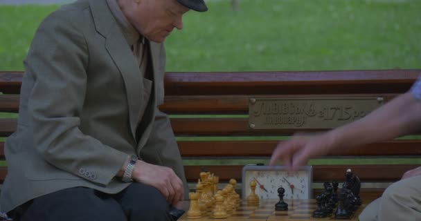 Two Men Are Sitting in Front of Each Other on The Bench, Playing Chess, Turn Chess Clocks on, Man is Pointing to Something, another Man Takes the Turn